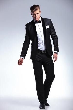 Photo pour full length picture of an elegant young fashion man in tuxedo posing, while looking at the camera. on gray background - image libre de droit