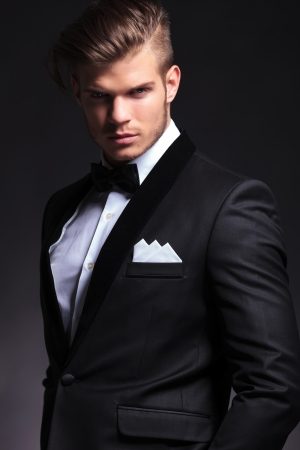 Photo pour portrait of an elegant young fashion man in tuxedo looking at the camera.on black background - image libre de droit