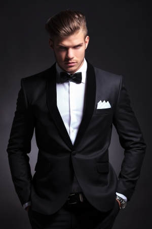 Foto de elegant young fashion man in tuxedo is holding both hands in his his pockets and looking at the camera.on black background - Imagen libre de derechos