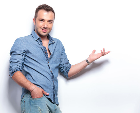 young casual man presenting something while holding a hand in his pocket and smiling for the camera. on white background