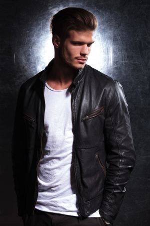 Foto de smiling fashion man wearing a leather jacket looking away from the camera, side view picture - Imagen libre de derechos