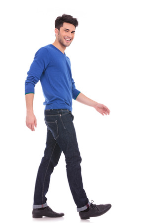 Photo for side view of a young man laughing and walking while looking at the camera, full body picture - Royalty Free Image