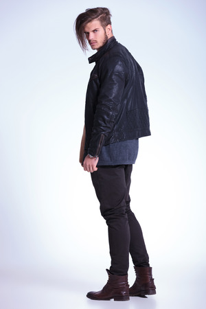 Photo for back view of a young fashion man in leather jacket looking at the camera - Royalty Free Image
