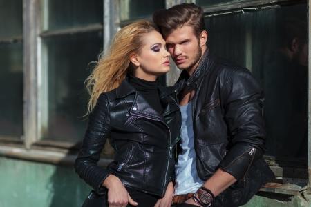 Foto de fashion couple in leather jackets posing against an old building outdoor - Imagen libre de derechos