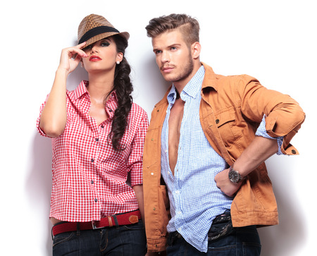Photo pour young casual fashion models posing in studio, woman looking at the camaera and man looking away to his side - image libre de droit