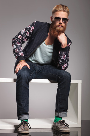 Foto de casual young man with a long red beard sitting like the thinker and looking into the camera. in a gray background studio - Imagen libre de derechos