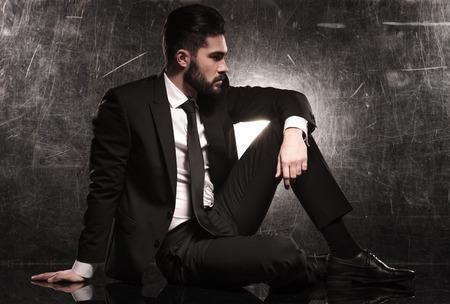 Photo pour side of an elegant business man in black suit and tie looking away  - image libre de droit