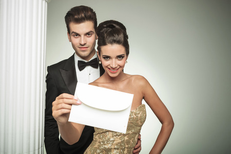 Photo pour happy young couple presenting an invite to their wedding, smiling nar a column in studio - image libre de droit