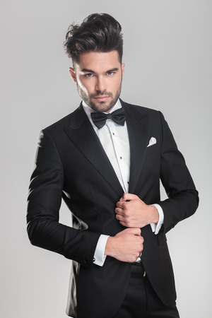 Photo pour Close up of an elegant young man ajusting his tuxedo while looking at the camera - image libre de droit