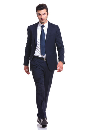 Photo pour Full length picture of a elegant business man walking on white background, looking at the camera - image libre de droit