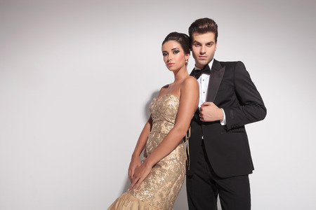 Photo for Elegant fashion couple posing against grey background, both looking at the camera. - Royalty Free Image