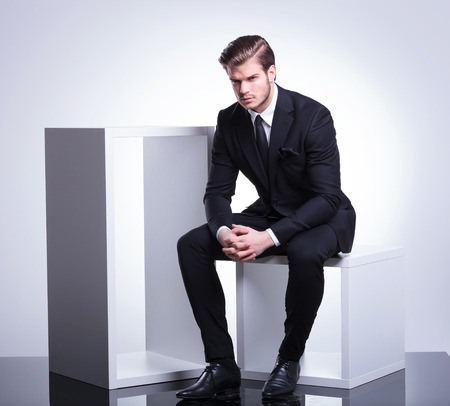 Photo pour Full body image of a handsome young business man sitting on a white cube holding his hand together, looking at the camera. - image libre de droit