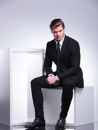 Photo pour Attractive young business man looking at the camera while sitting on a white modern chair. - image libre de droit