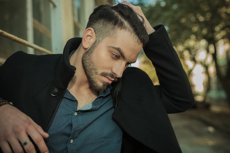 Photo pour Casual fashion man looking down while fixing his hair, close up picture. - image libre de droit