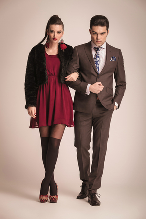 Full length picture of a young fashion couple posing together holding each others arm. The man is holding his hand in his pocket.