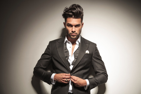 Photo pour Handsome elegant business man looking at the camera while unbuttoning his jacket. - image libre de droit