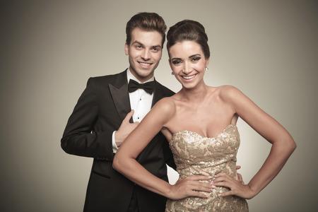 Foto de Happy elegant couple laughing while looking at the camera. - Imagen libre de derechos