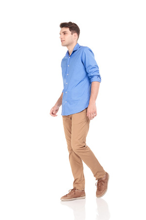 Photo pour Side view of a young fashion man walking on isolated background. - image libre de droit