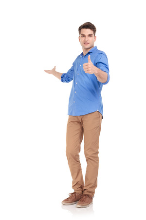 Foto de Full body picture of a young fashion man welcoming you while showing the thumbs up gesture. - Imagen libre de derechos