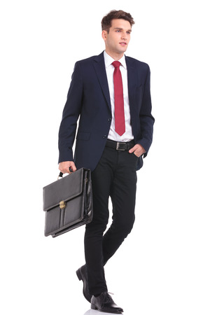 Foto de Side view of a handsome young business man walking with his hand in pocket while holding a briefcase. - Imagen libre de derechos