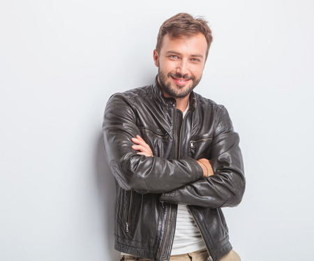 Photo for confident young man in leather jacket is standing with arms crossed against studio background - Royalty Free Image