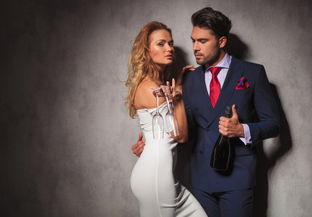 Foto für side view of a hot couple holding a bottle of champagne , man is looking at his woman while she is holding two glasses - Lizenzfreies Bild