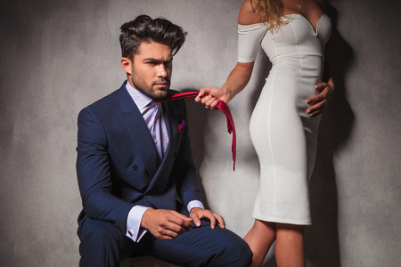 Photo pour sexy blonde woman is pulling her lover by his tie, man looks angry and dramatic - image libre de droit