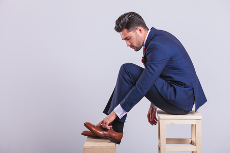 Photo pour hansome man in suit sitting on chair in studio cleaning his brogue shoes - image libre de droit