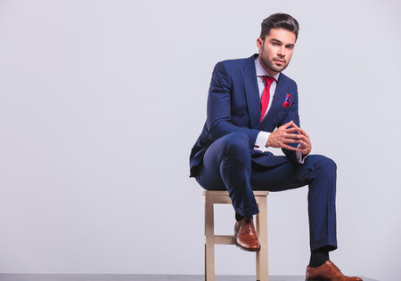 Photo for elegant man in business suit sitting in studio with palms touching while resting his leg on chair - Royalty Free Image