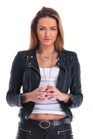portrait of young blonde girl in leather jacket posing in white studio background while touching hands and looking at the camera