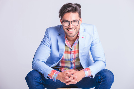 Foto de close portrait attractive man posing seated with legs spread open and hands touching, while smiling at the camera in studio background - Imagen libre de derechos