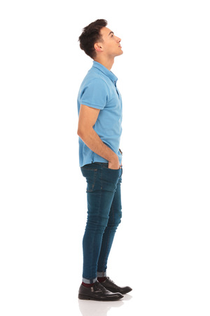 Photo pour side portrait of young man in blue shirt looking up with hands in pockets while posing in isolated studio background - image libre de droit