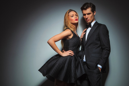 Photo pour elegant couple in black posing together in gray studio background. - image libre de droit