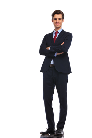 Photo for successful young business man standing with hands crossed on white studio background - Royalty Free Image