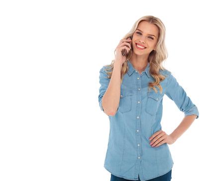 Foto de happy smiling blonde casual woman talking on the phone on white background - Imagen libre de derechos
