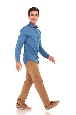Photo for side view of a walking smiling casual man on white studio background - Royalty Free Image