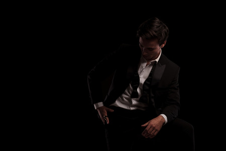 Photo pour man in tuxedo is looking down to his ring on black background - image libre de droit