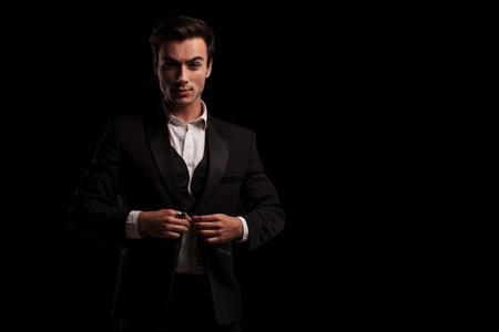 Photo pour young businessman in tuxedo buttoning his coat on black background - image libre de droit