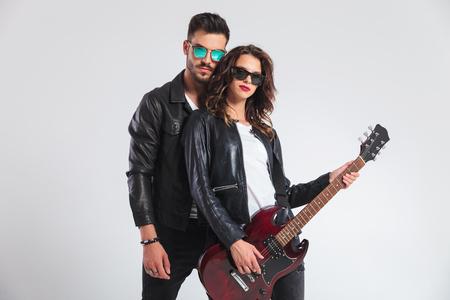 Foto de punk man behind his woman playing electric guitar on grey background - Imagen libre de derechos