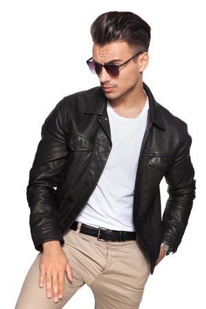 Foto de young sexy man looks down to a side on white background; he wears leather jacket and sunglasses  - Imagen libre de derechos