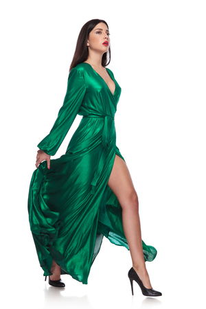 Photo pour sensual woman in fluttering long green dress walks to side while holding it, on white background, full body picture - image libre de droit
