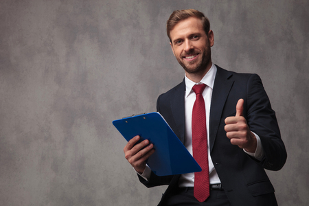 Photo for smiling young businessman holding a clipboard makes the ok sign on studio background - Royalty Free Image