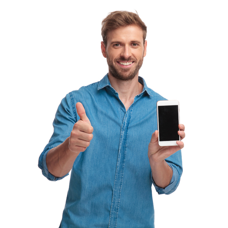 Foto de smiling casual man showing the blank screen of his phone and makes the ok sign on white background - Imagen libre de derechos