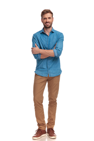 Photo for confident smiling casual man with hands crossed in a full body pose on white background - Royalty Free Image