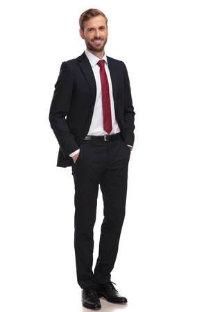 Photo pour relaxed businessman smiling and standing with hands in pockets on white background - image libre de droit