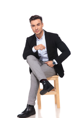 Photo pour attractive businessman sitting on wooden chair with legs crossed on white background and resting his elbow on knee - image libre de droit