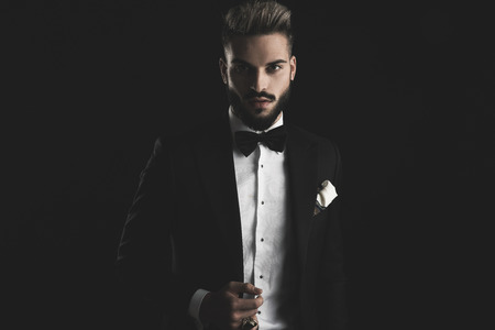 Photo pour man in tuxedo with bowtie and white hankerchief adjusting his lounge jacket on black background - image libre de droit