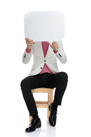 Foto de elegant businessman holding speech bubble over his face while sitting on chair on white background - Imagen libre de derechos