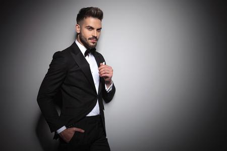 Foto de handsome young guy in black tuxedo holding hand in pocket on dramatic studio background - Imagen libre de derechos