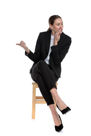 Photo for pretty businesswoman wearing black suit sitting  with crossed legs and whispering to a side while pointing the other against white studio background - Royalty Free Image